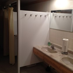 Downstairs bathroom, 2 sinks, 3 shower stalls, 3 bathroom stalls
