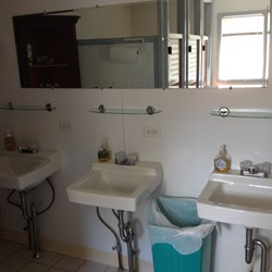Upstairs communal bath has 3 sinks, 3 bathroom stalls, and 2 shower stalls